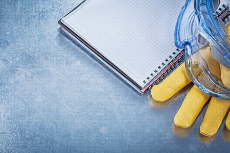 protective goggles: Protective goggles leather gloves copybook on metallic background construction concept.