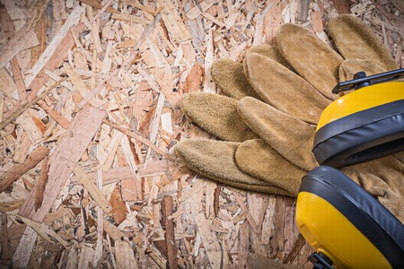 leather gloves: Protective leather gloves earmuffs on chipboard. Stock Photo