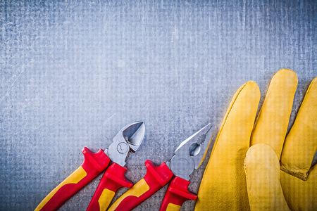 dielectric: Yellow safety gloves metal pliers wire-cutter electricity concept.