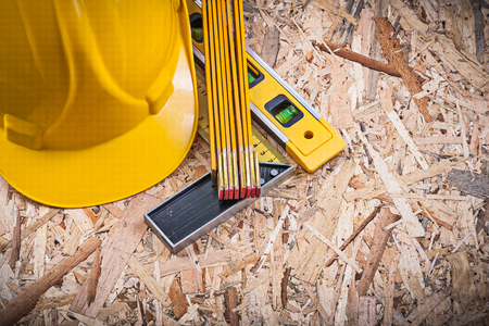 Square ruler construction level wooden meter hard hat on chipboard. Stock Photo