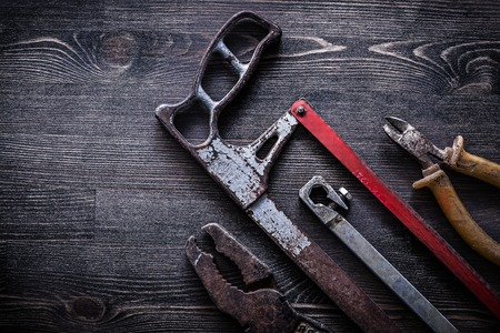 obsolete: Obsolete vintage handsaw wire-cutter pliers on wooden board construction concept. Stock Photo