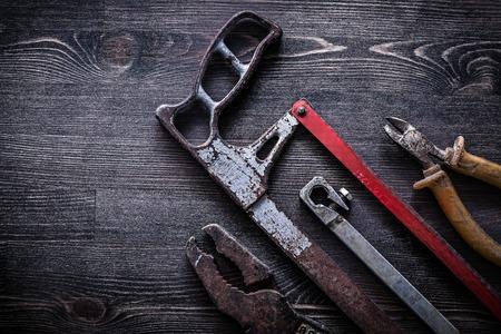 serrucho: serrucho vendimia alicates de corte de alambre obsoletas sobre el concepto de construcción plancha de madera.