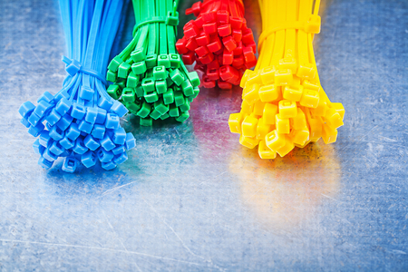 cable tie: Multicolored plastic tying cables on scratched metallic background.
