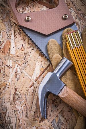 serrucho: Protective leather gloves wooden meter handsaw claw hammer on OSB. Foto de archivo