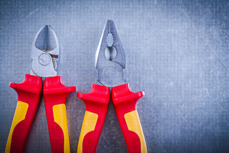 dielectric: Pliers nippers on metallic background horizontal image electricity concept. Stock Photo