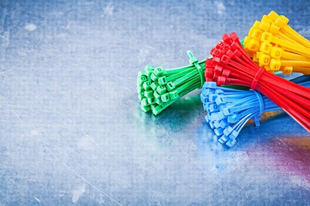 Multicolored plastic cable ties on metallic background construction concept.