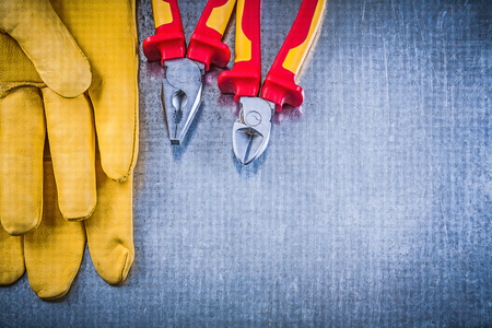 safety gloves: Yellow safety gloves pliers wire-cutter on metallic background electricity concept. Stock Photo
