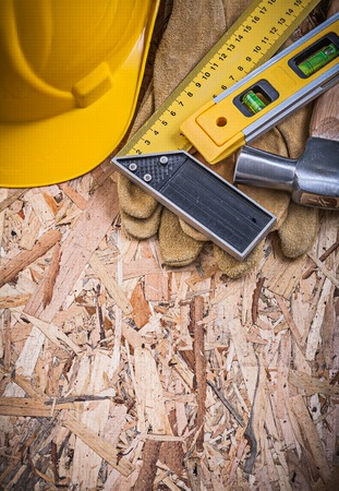 construction level: Square ruler construction level hammer yellow hard hat leather gloves. Stock Photo