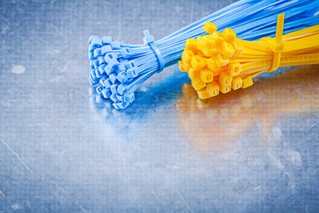cable tie: Plastic self-locking tying cables on metallic background construction concept. Stock Photo