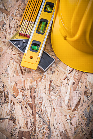 square ruler: Square ruler construction level building helmet wooden meter on chipboard. Stock Photo