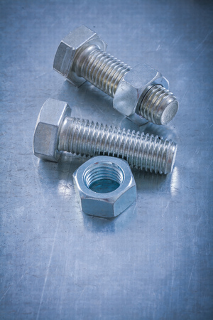 threaded: Stainless threaded bolts screw-nuts on metallic background maintenance concept. Stock Photo