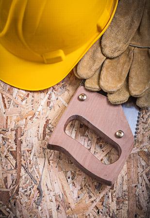 serrucho: guantes de cuero de seguridad en edificios sierra de mano casco en OSB. Foto de archivo