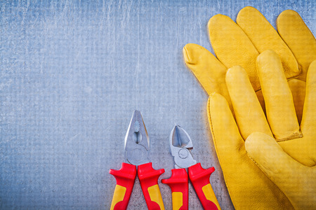 nippers: Leather safety gloves pliers nippers on metallic background electricity concept. Stock Photo