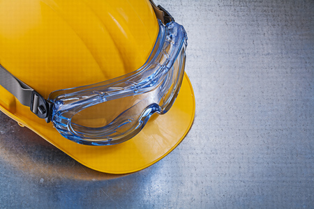 Safety glasses hard hat on metallic background construction concept.