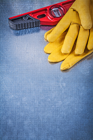 construction level: Construction level safety gloves on scratched metallic background copyspace. Stock Photo