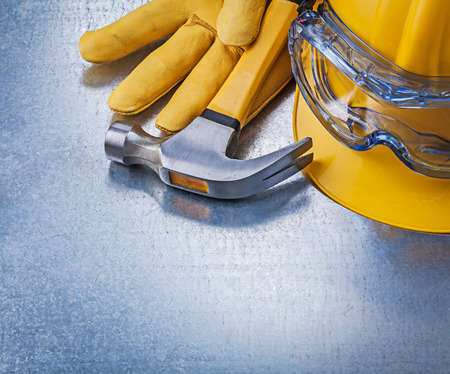 protective spectacles: Safety glasses hard hat leather gloves claw hammer construction concept.