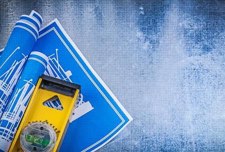 blueprint: Blue rolled blueprints yellow construction level on metallic background.