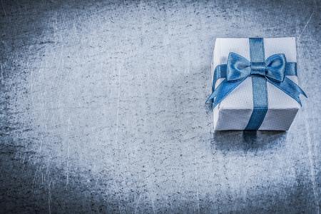 giftbox: Giftbox present bow on metallic background holidays concept. Stock Photo