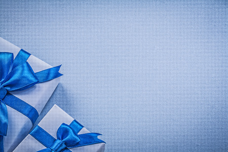 blue background: Packaged present boxes on blue background greeting card holidays concept.