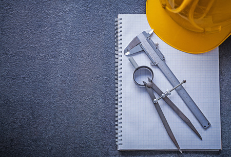 compas de dibujo: Notebook building helmet drawing compass slide caliper construction concept. Foto de archivo