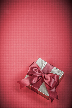 anniversary: Present container with tied ribbon on red background holidays concept.