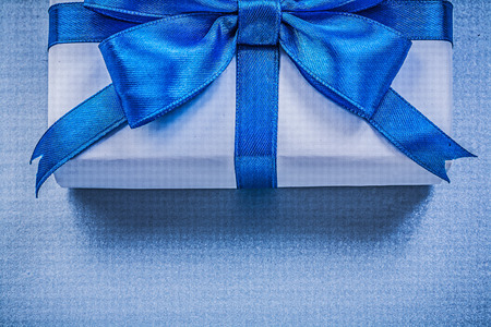 Giftbox with tied ribbon on blue background holidays concept.