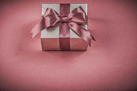 red glittery: Packed gift container on red background holidays concept.