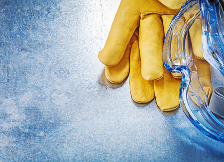 protective spectacles: Safety spectacles gloves on scratched metallic background construction concept. Stock Photo