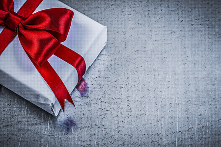 giftbox: Giftbox with red ribbon on metallic background holidays concept.