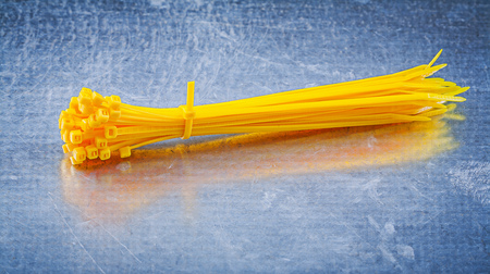cable tie: Yellow plastic self-locking cable ties on metallic background construction concept.
