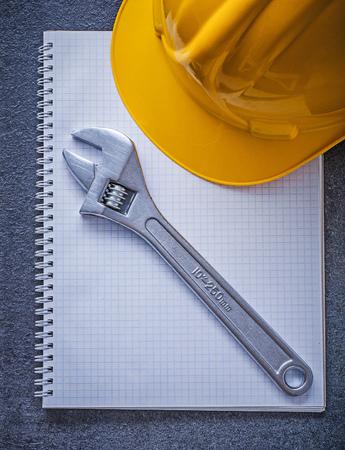 hard hat: Notebook hard hat adjustable spanner construction concept. Stock Photo