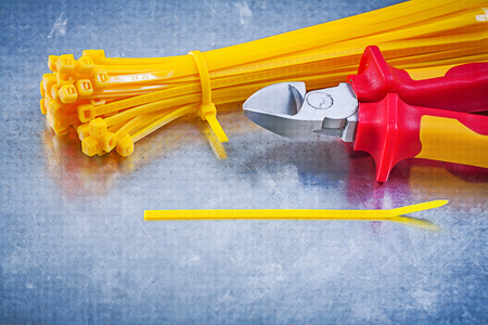 cable cutter: Cutting pliers yellow cable ties on metallic background construction concept.