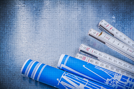 blue metallic background: Blue rolled construction drawings wooden meter on scratched metallic background.