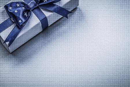 blue background: Gift container with bow on blue background holidays concept.