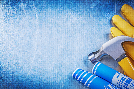 claw hammer: Protective working gloves blue rolled construction drawings claw hammer.