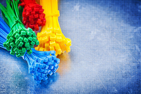 zip tie: Set of multicolored plastic tying cables on scratched metallic background.