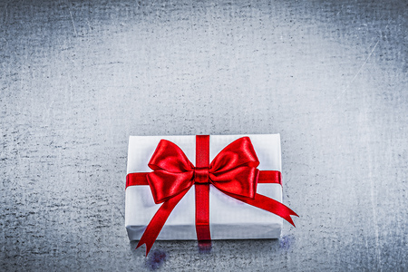 wrapped present: Wrapped present with red bow on metallic background holidays concept.