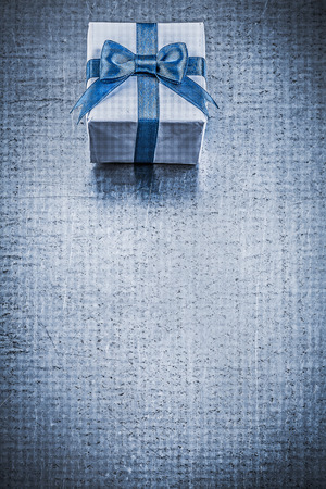 giftbox: Giftbox blue bow on metallic background vertical image holidays concept.