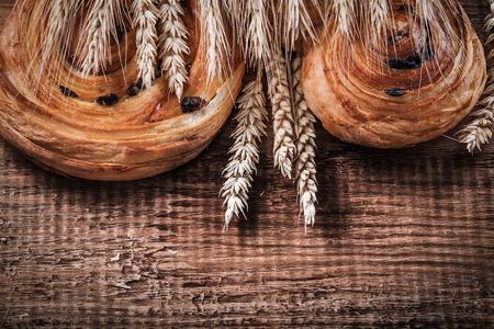 oaken: Heap of wheat ears sweet raisin bakery on oaken wooden board food and drink concept. Stock Photo