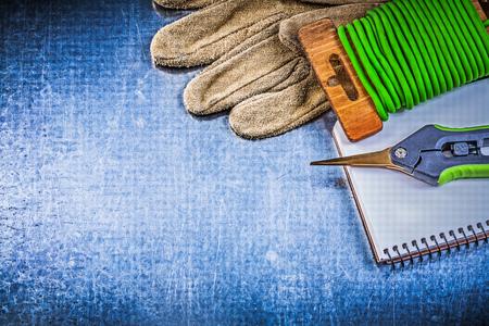 workbook: Soft twist tie garden pruner protective gloves workbook on metallic background.