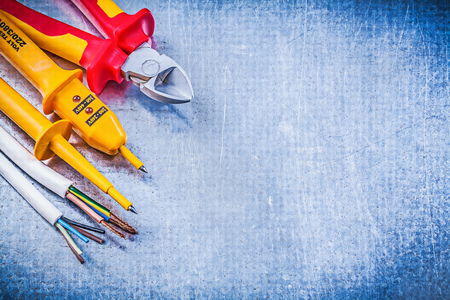 dielectric: Yellow electrical tester wires nippers on metallic background copy space electricity concept. Stock Photo