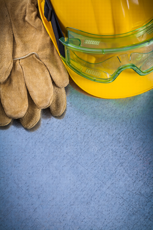protective eyewear: Protective leather gloves yellow building helmet and safety eyewear on scratched metallic background construction concept. Stock Photo