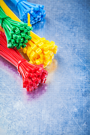 cable tie: Multicolored plastic self-locking tying cables on metallic background construction concept.