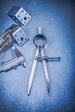 bar tool set: Metal lock jaw pliers trammel caliper drilled angle bars construction divider on metallic background.