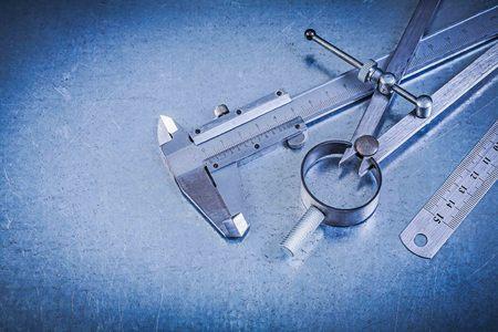 compas de dibujo: Construcción metálica dibujo brújula gobernante vernier en el fondo metálico. Foto de archivo