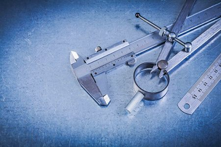 vernier caliper: Metal construction drawing compass ruler vernier caliper on metallic background.