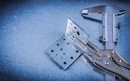 angle bar: Adjustable pliers wrench vernier caliper angle bracket on metallic background.