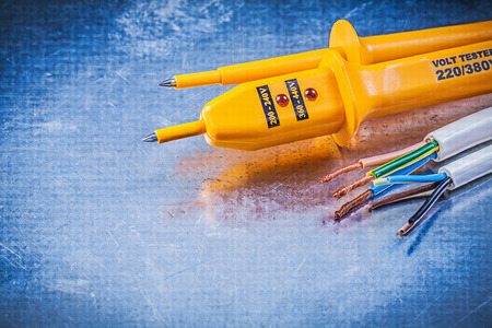 electricity background: Yellow electrical tester wires on metallic background electricity concept. Stock Photo