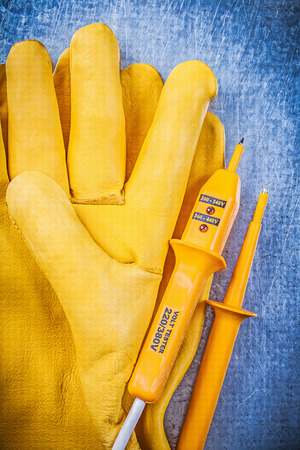 protective gloves: Yellow electrical tester protective gloves on metallic background vertical view electricity concept. Stock Photo