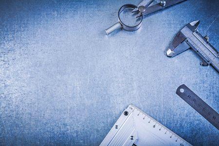 compas de dibujo: Dibujo de construcción de metal brújula gobernante vernier tratar cuadrado sobre fondo metálico. Foto de archivo